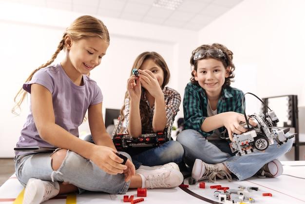 Веселимся вместе. веселые, веселые, игривые дети сидят в классе и играют с гаджетами и устройствами, выражая свое счастье