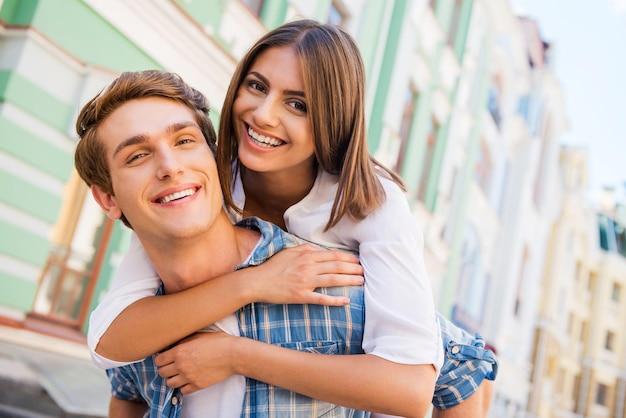 함께 재미. 여자가 남자친구를 껴안고 웃고 있는 동안 야외에서 함께 서 있는 아름다운 젊은 사랑의 커플의 낮은 각도 보기