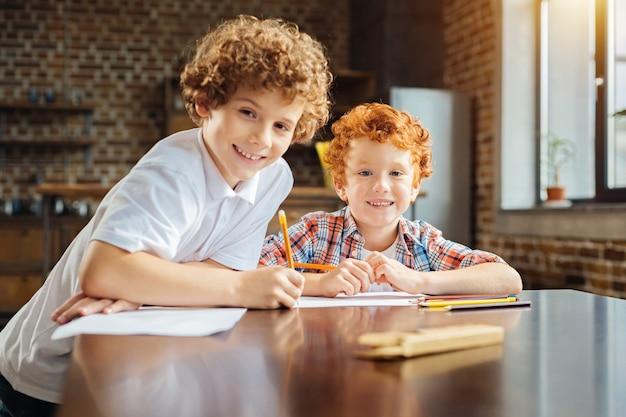 Веселимся вместе. селективный фокус на рыжем мальчике, который смотрит в камеру и радостно сияет, проводя время со своим старшим братом и рисующим.
