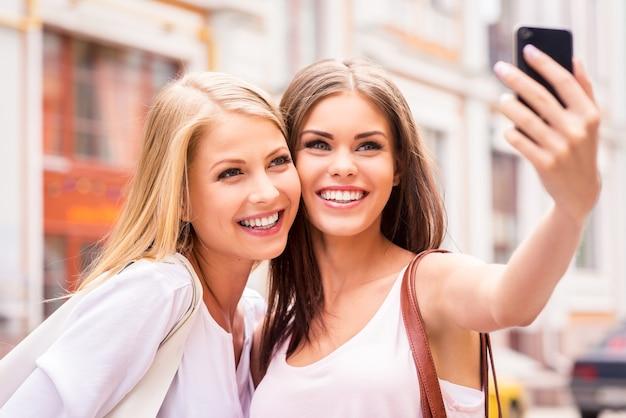 함께 재미. 셀카를 만들고 야외에 서 있는 동안 웃는 두 명의 아름다운 젊은 여성