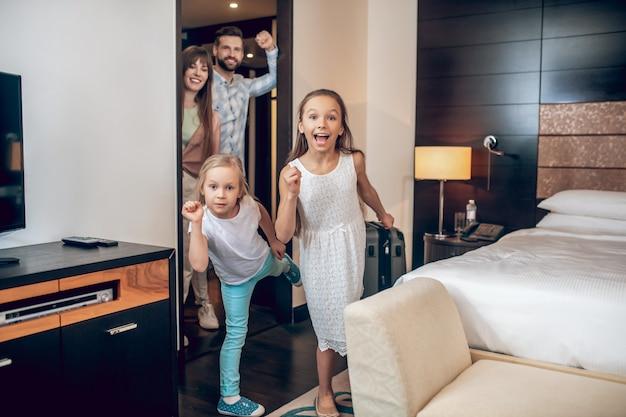 Веселиться. две девочки веселятся в комнате, родители смотрят на них