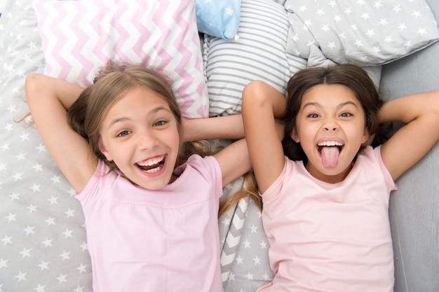 親友と楽しんでください。一緒に楽しんでいる子供たちの遊び心のある陽気な気分。パジャマパーティーと友情。寝室でリラックスした姉妹幸せな小さな子供たち。小さな女の子の友情。余暇と楽しみ。