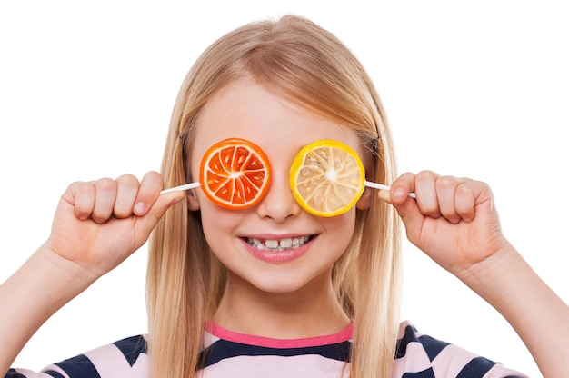 사탕과 함께 재미. 사탕으로 눈을 덮고 흰색으로 격리된 채 웃고 있는 쾌활한 어린 소녀