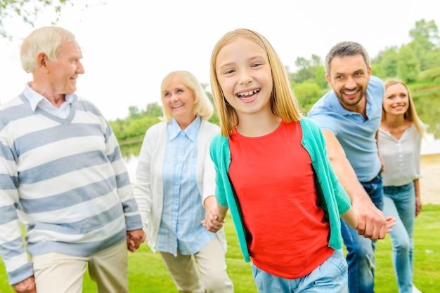 家族と一緒に楽しんでください。一緒に屋外を歩きながら家族との時間を楽しんでいる幸せな少女