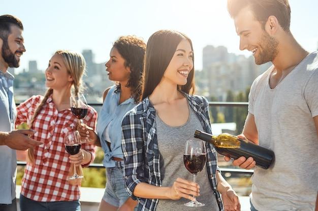 友達と楽しんでいる若いひげを生やした男性は彼の友達にワインを注いで笑っています