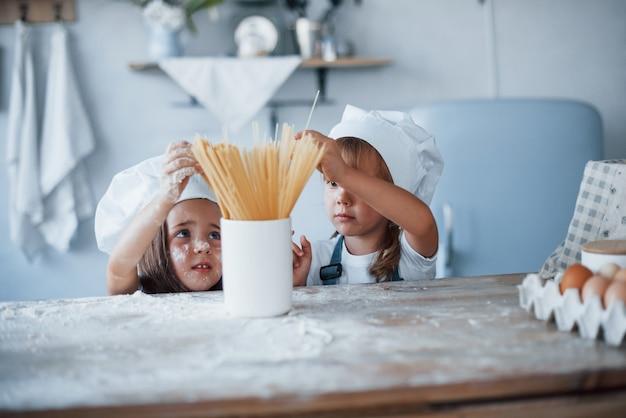 Having fun with spaghetti. family kids in white chef uniform preparing food on the kitchen.