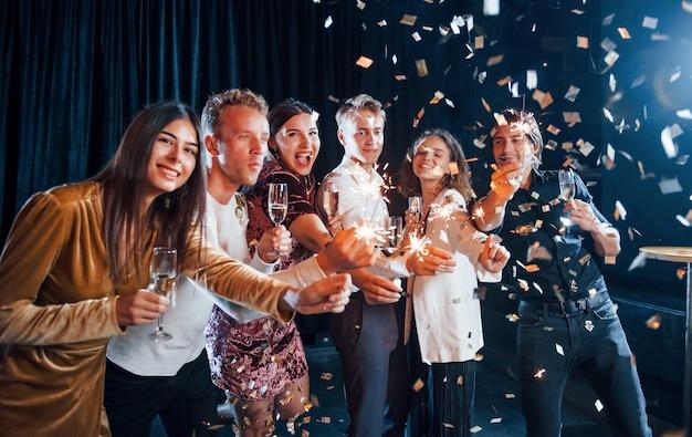 線香花火を楽しんでください。紙吹雪が空中にあります。飲み物を片手に屋内で新年を祝う陽気な友人のグループ。