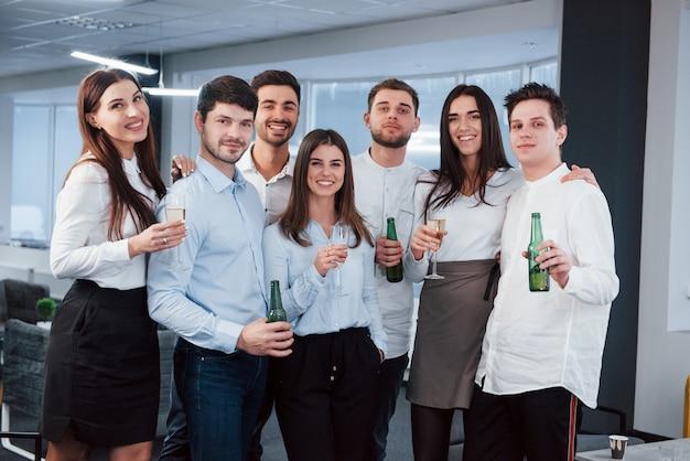 楽しい時間を。モダンな明るいオフィスで飲み物を保持している古典的な服の若いチームの写真