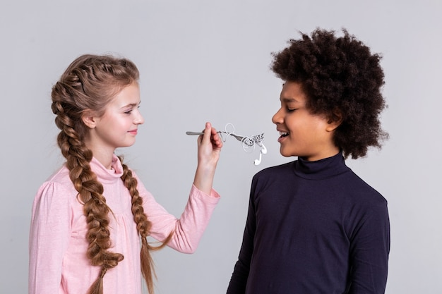 Having grey background. weird long-haired girl proposing her friend fork with rolled headphones on it while he looking confused