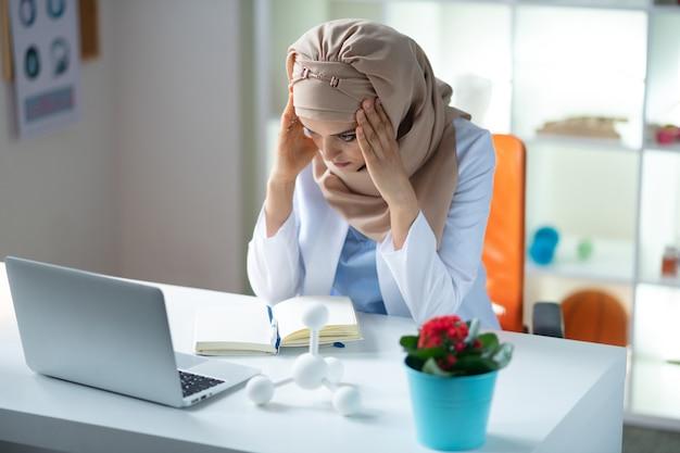 두통이 있습니다. 하루 종일 일한 후 두통이있는 히잡을 착용 한 의료 과학자