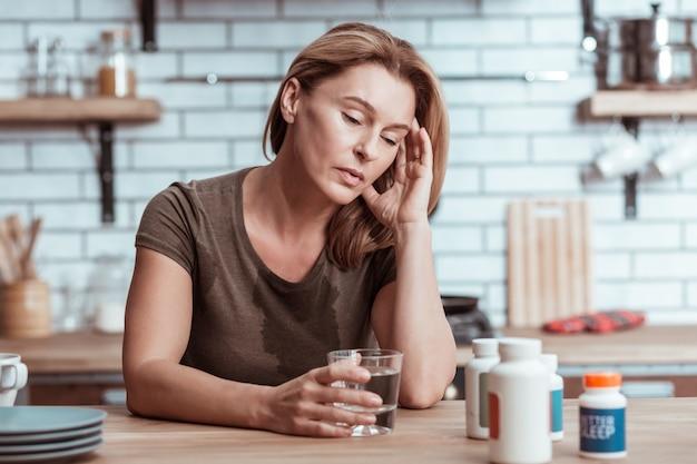 心痛む。 tシャツに水をこぼす心痛を持つ金髪の落ち込んでストレスを感じた女性