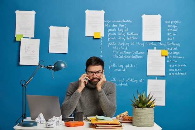 Having important conversation. serious bearded male worker sits at desktop and talks via cell phone, being involved in work, discusses remote project with coworker distantly, papers hanging on wall