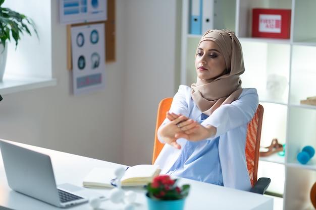 Небольшой перерыв. женщина-химик в хиджабе с небольшим перерывом после слишком долгой работы