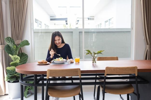 Имея концепцию еды симпатичная женщина, смешивающая заправку для салата с нулевым содержанием калорий с зеленым салатом в миске.