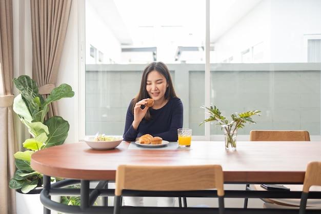食事のコンセプトを持って、ダイニングルームのテーブルで彼女のお気に入りのデザートを鑑賞する笑顔の女性。