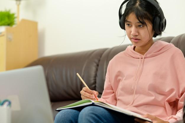 オンラインレッスンを受けるアジアの子供たちは自宅でeラーニングを使って自習します。オンライン教育と自己学習とホームスクーリングの概念。