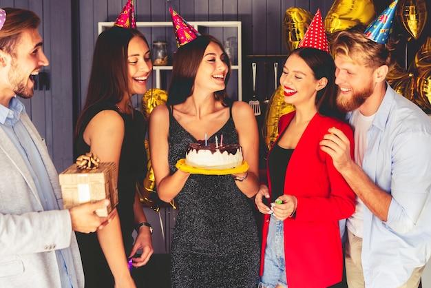 パーティーをする。バースデーケーキの周りの若者。女性の周りにはお祝いを待っているゲストがいます