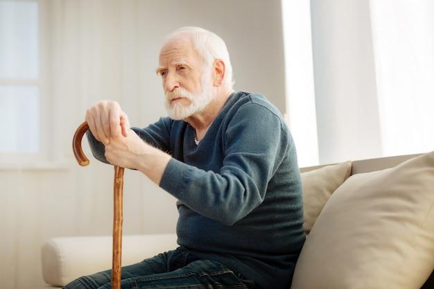 문제가 있습니다. 집중된 수염 된 회색 머리 남자가 이마를 주름과 기대하는 동안 지팡이에 기대어
