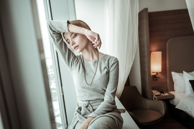 Having rest. elegant woman wearing grey dress and accessories having rest at home after work