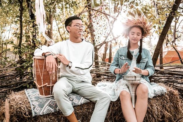 休む。音楽を聴きながら彼のパートナーの近くに座っている幸せなアジア人