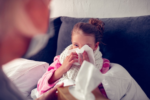 Having running nose. little dark-haired girl staying in bed using napkin while having running nose