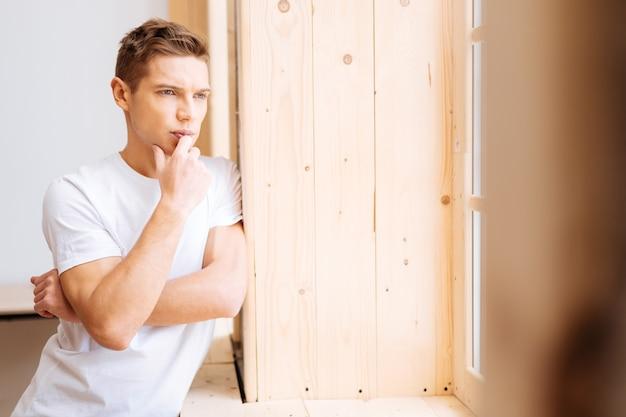 Проблемы. красивый встревоженный хорошо сложенный молодой человек думает, трогает подбородок и смотрит в окно