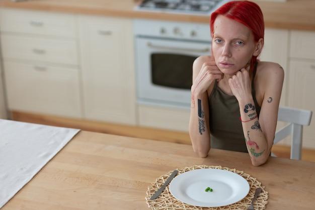 Нездоровый вид. татуированная рыжеволосая женщина страдает анорексией и имеет нездоровый вид