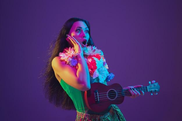 네온 불빛에 보라색 벽에 하와이 여성 댄서.