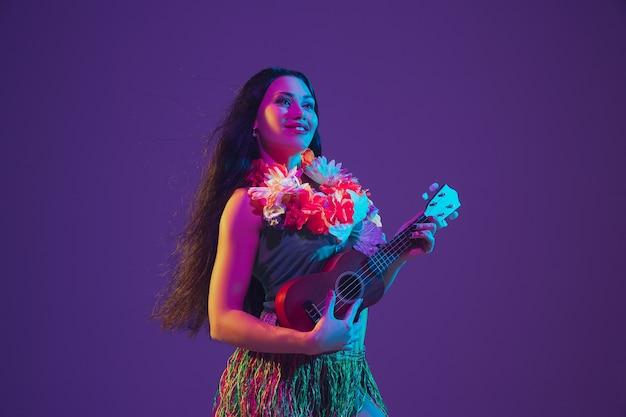 Ballerina hawaiana sulla parete viola alla luce al neon.