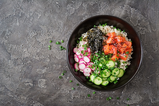Hawaiian fish poke bowl with rice, radish, cucumber, tomato, sesame seeds and seaweeds.