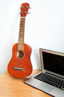 Hawaiian four-string guitar ukulele on wooden table and laptop.