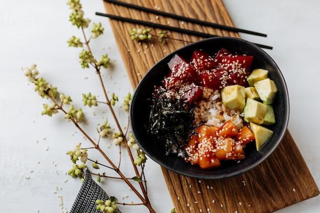 Гавайский салат из свежего тунца с овощами подается на черной тарелке.