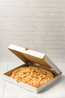 Hawaiian pizza in a cardboard box on a white brick wall background with copy space.