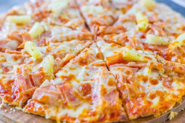 Гавайская пицца - это итальянская еда, которую готовят с томатным соусом, нарезанными ананасами, ветчиной и сыром.
