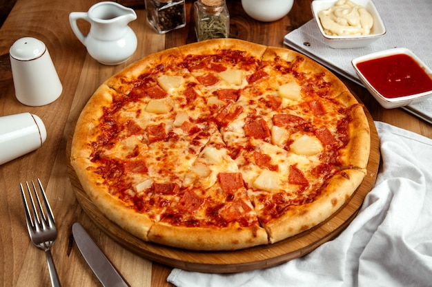 Hawaiian pizza with cooked ham pizza sauce cheese and pineapple Free Photo