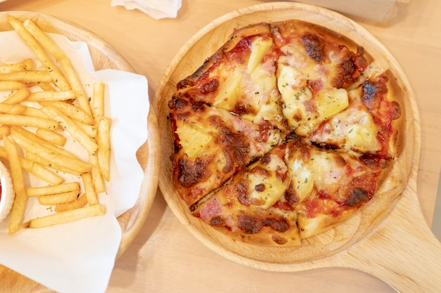 Hawaiian pizzeria and french fries on the table in the restaurant