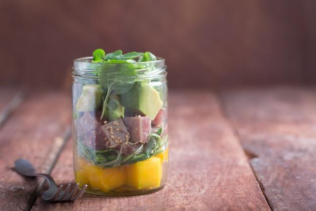 Hawaiian poke salad with tuna, avocado and vegetables in a jar