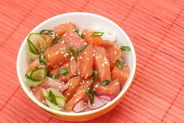 Hawaiian poke with salmon and sesame seeds, boiled rice, fresh cucumber, radish and green onions in a bowl on the red bamboo napkin