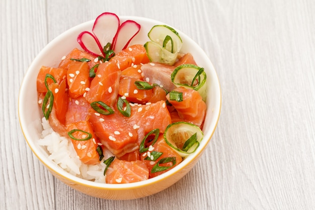 Hawaiian poke with salmon and sesame seeds, boiled rice, fresh cucumber, radish and green onions in a porcelain bowl