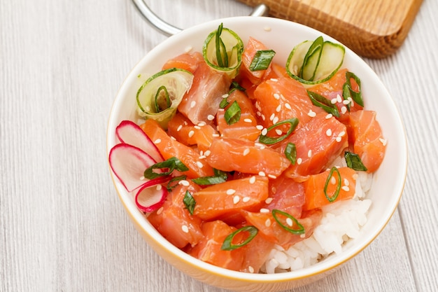 Hawaiian poke with salmon and sesame seeds and green onions in bowl with wooden cutting board