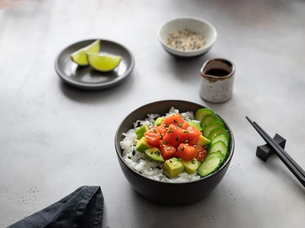 ハワイアンサーモンフィッシュポークボウルアボカド、キュウリ、米、ごま、醤油、灰色の背景に。伝統的なアジア料理。