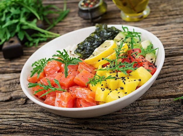 ハワイ産サーモンフィッシュポークボウルにご飯、アボカド、マンゴー、トマト、ゴマ、海藻を添えて。仏bowl。ダイエット食品。