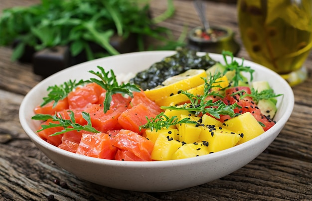 Hawaiian salmon fish poke bowl with rice, avocado, mango, tomato, sesame seeds and seaweeds. buddha bowl. diet food.