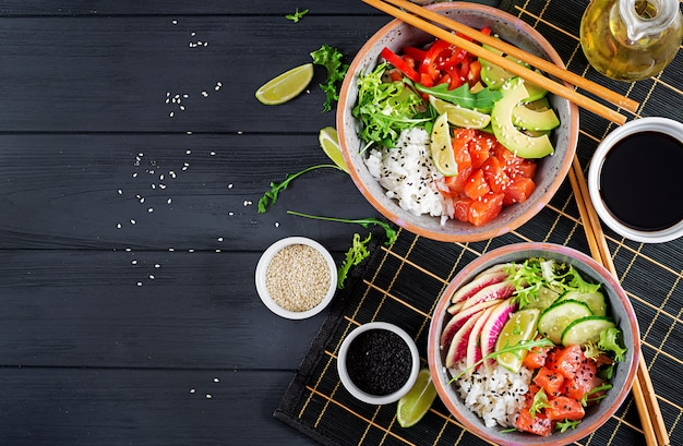 Hawaiian salmon fish poke bowl with rice, avocado, paprika, cucumber, radish, sesame seeds and lime.