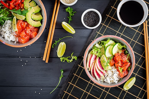 Hawaiian salmon fish poke bowl with rice, avocado, paprika, cucumber, radish, sesame seeds and lime.