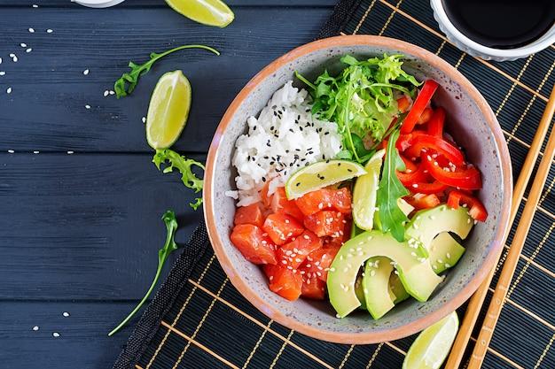 Hawaiian salmon fish poke bowl with rice, avocado, paprika, sesame seeds and lime. bu