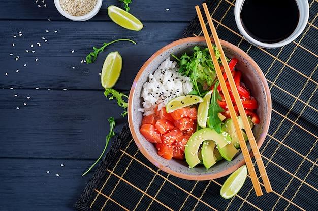 Hawaiian salmon fish poke bowl with rice, avocado, paprika, sesame seeds and lime. buddha bowl. diet food. top view