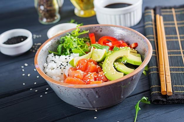 Hawaiian salmon fish poke bowl with rice, avocado, paprika, sesame seeds and lime. buddha bowl. diet food.