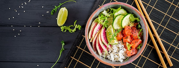 Hawaiian salmon fish poke bowl with rice, cucumber, radish, sesame seeds and lime. buddha bowl. diet food. banner.  top view