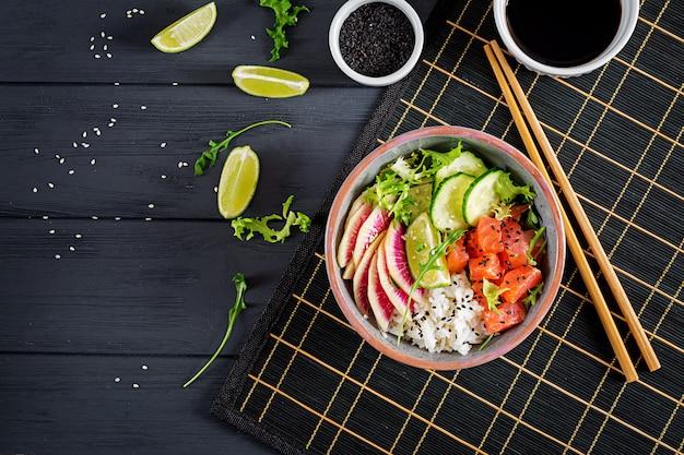 Hawaiian salmon fish poke bowl with rice, cucumber, radish, sesame seeds and lime. buddha bowl. diet food. top view